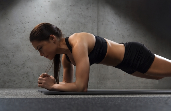 15545443-woman-doing-plank-exercise-on-mat-in-gym