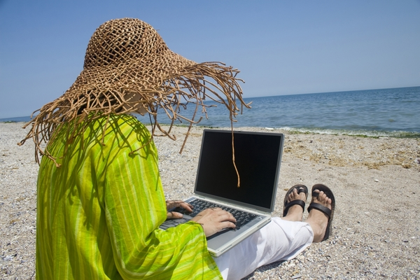 387531-woman-sitting-on-beach-with-laptop