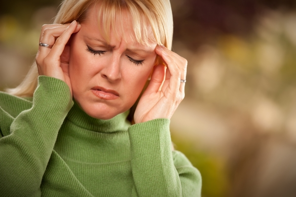 1093386-grimacing-woman-suffering-a-headache