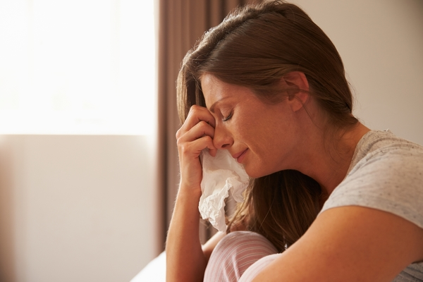 13113363-woman-suffering-from-depression-sitting-on-bed-and-crying
